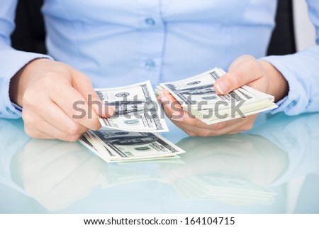 Close-up Of A Businesswoman Counting Bank Note At Desk - stock photo