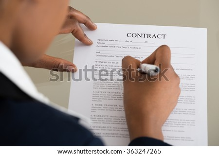 Close-up Of A Businesswoman Filling Contract Form - stock photo