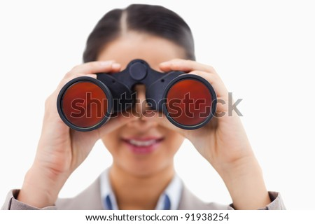 Close up of a businesswoman looking through binoculars against a white background - stock photo
