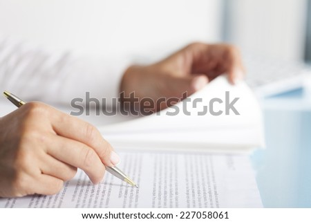 Close-up of a businesswoman's hand with a pen writing something. - stock photo
