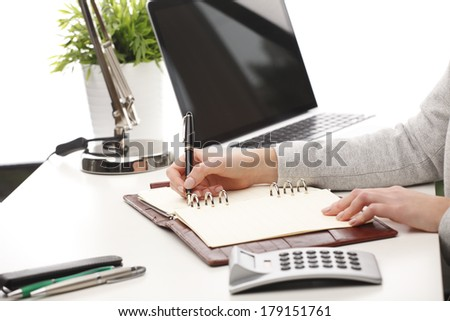 Close-up of a businesswoman sitting at desk and analyzing data in office.
