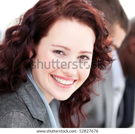 Close-up of a businesswoman smiling at the camera in a meeting with her team