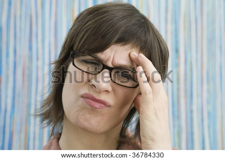 Close-up of a businesswoman suffering from a headache - stock photo