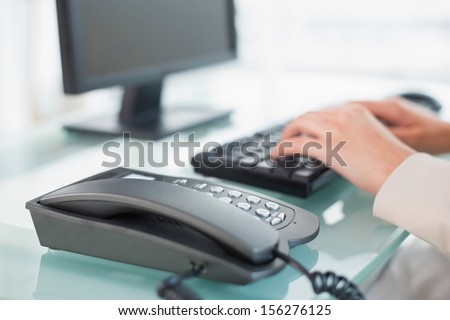 Close up of a businesswoman typing on a keyboard at office
