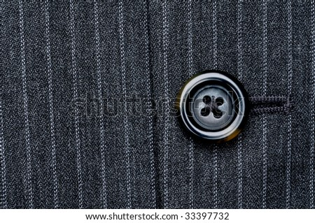 Close up of a button on a pin striped business suit coat - stock photo
