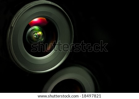 Close-up of a camera objective on a black background with reflection - stock photo