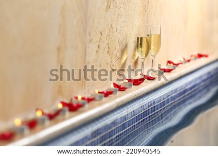Close up of a candles and rose petals wit a champagne cups in a spa celebration concept - stock photo