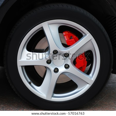 Close up of a car wheel with red brake - stock photo