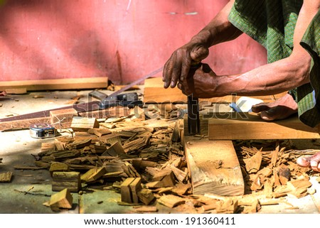 Close up of a carpenter chisel on a wooden plank - stock photo