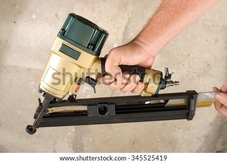 Close up of a carpenter's hands replacing nails in an angle nail gun - stock photo