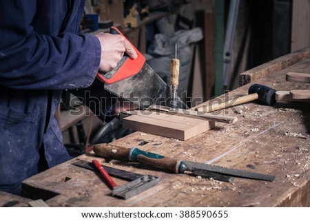 Close-up of a Carpenter Sawing a Piece of Wood with a Handsaw in his Workshop; Selective Focus - stock photo
