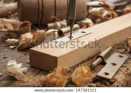 close up  of a carpenter screwed a hinge on a wooden plank - stock photo