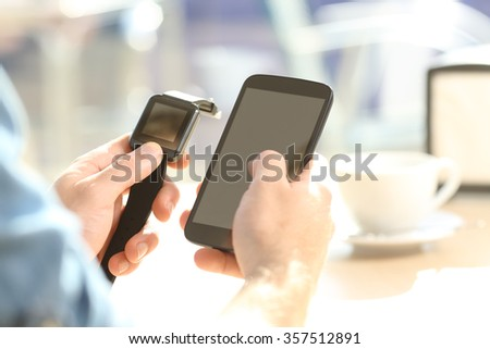Close up of a casual man hands synchronizing a generic smartwatch and mobile phone in a bar terrace - stock photo