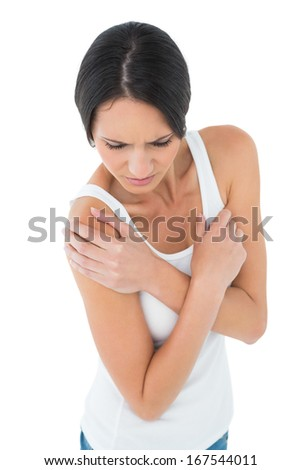 Close-up of a casual young woman with shoulder pain over white background - stock photo