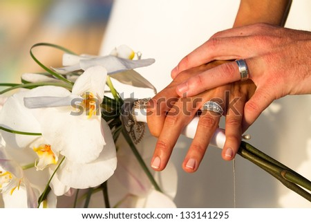 Close up of a caucasian couple's hands with wedding rings