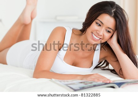 close up of a charming woman lying on bed reading a magazine in bedroom - stock photo