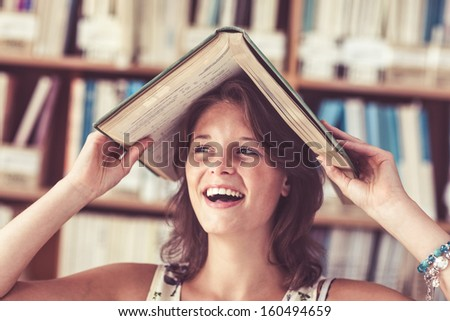 Close-up of a cheerful female student holding book over her head in the library - stock photo