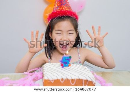 Close-up of a cheerful little girl at her birthday party - stock photo