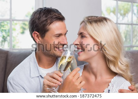 Close-up of a cheerful loving young couple with champagne flutes at home