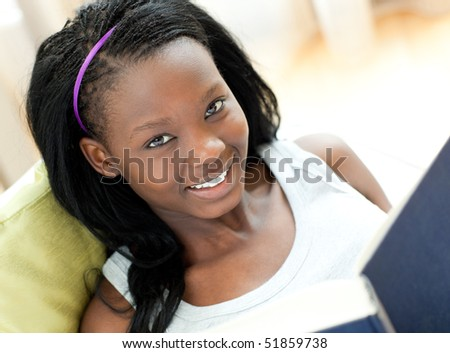 Close-up of a cheerful woman studying lying on a sofa at home - stock photo