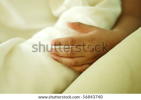 Close up of a child's hand in a bed. - stock photo