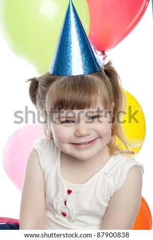 close up of a child smiling. The girl has a blue Party hat on her head