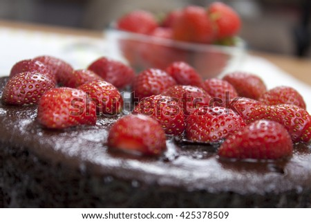 Close up of a chocolate fudge cake topped with fresh ripe strawberry's on a table - stock photo