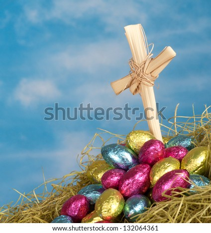 Close Up Of A Christian Cross And Bright Colorful Chocolate Easter Eggs In Mound