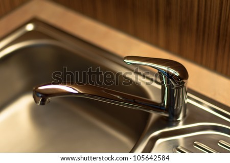 close-up of a chrome water faucet in a wooden kitchen