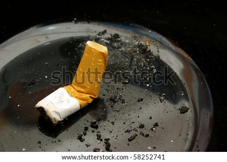 close-up of a cigarette butt smashed in a black ashtray - stock photo