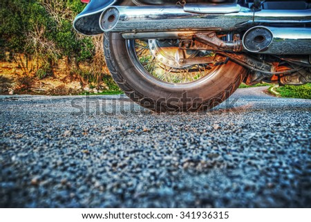 close up of a classic motorcycle wheel seen from the ground in hdr - stock photo