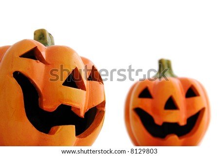 Close up of a clay Halloween pumpkin with one out of focus one in the background