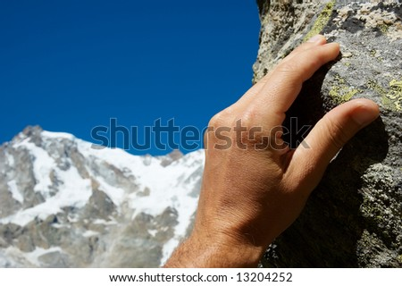 Close-up of a climber's hand; in background the snowy high peak of Monte Rosa, Italy. Blue copy-space in the up-left area. - stock photo