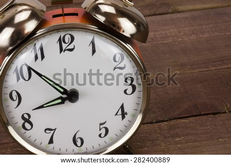 Close up of a clock against a wooden background