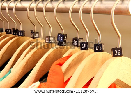 Close up of a clothing rack with wooden hangers showing different clothing size tags - stock photo