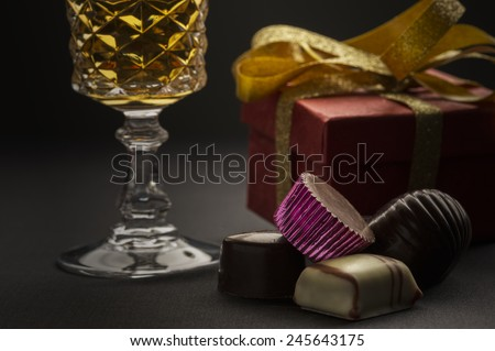 Close up of a cluster of delicious handmade luxury chocolates with a goblet of white wine and a gift with golden bow in a concept of a romantic anniversary, Christmas or Valentines day - stock photo