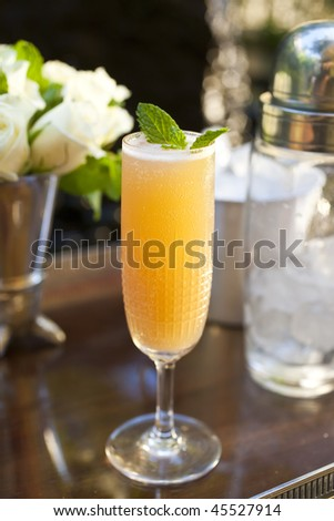 Close-up of a cocktail on a counter, with a bouquet of white flowers in the background. Vertical format. - stock photo