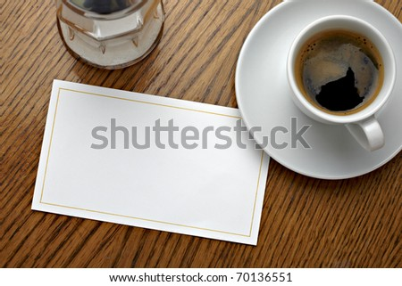 close up of a coffee cup and a blank card on a table - stock photo