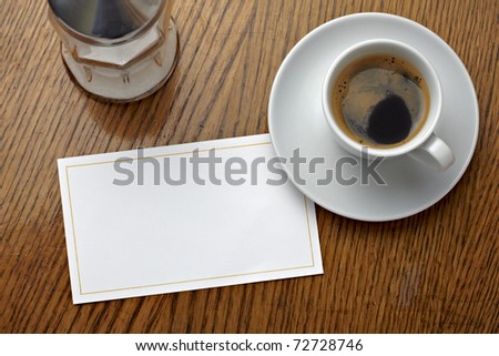 close up of a coffee cup and a blank card on a table