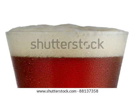 Close up of a cold frosted pilsner beer glass with dark ale and head just above rim level - stock photo