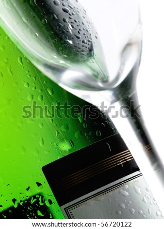 Close-up of a cold wet bottle of alcoholic drink with glass(focus on bottle) - stock photo