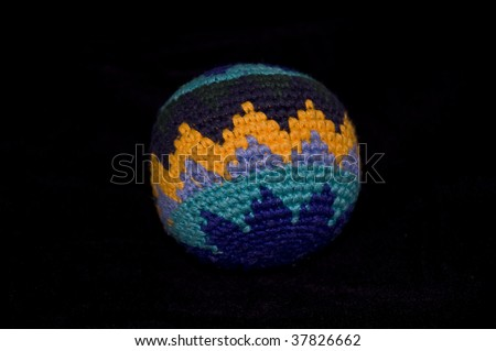 Close Up of a Colorful Hacky-Sack Isolated on Black - stock photo
