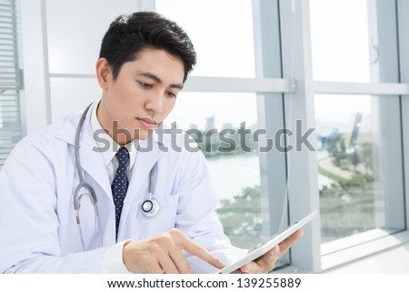 Close-up of a concentrated doctor working with a touchpad - stock photo