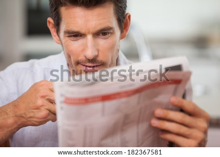 Close-up of a concentrated young man reading newspaper at home - stock photo
