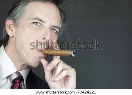 Close-up of a confident businessman smoking a cigar, side view. - stock photo
