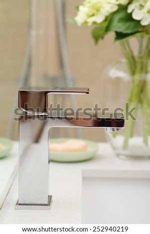 Close up of a contemporary square shaped bathroom mixer tap - stock photo
