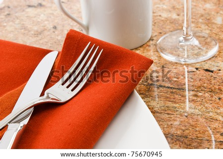 Close up of a contemporary table setting showing silverware, mug and wine goblet with copy space - stock photo