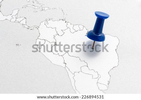 Close-up of a contour map of South America with a blue pin on Brazil. - stock photo