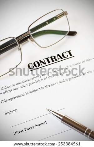 Close up of a contract ready to be signed.With pen and glasses.Office,legal concept.With vignette