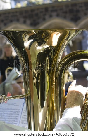 Close up of a copper tuba in hand of the musician